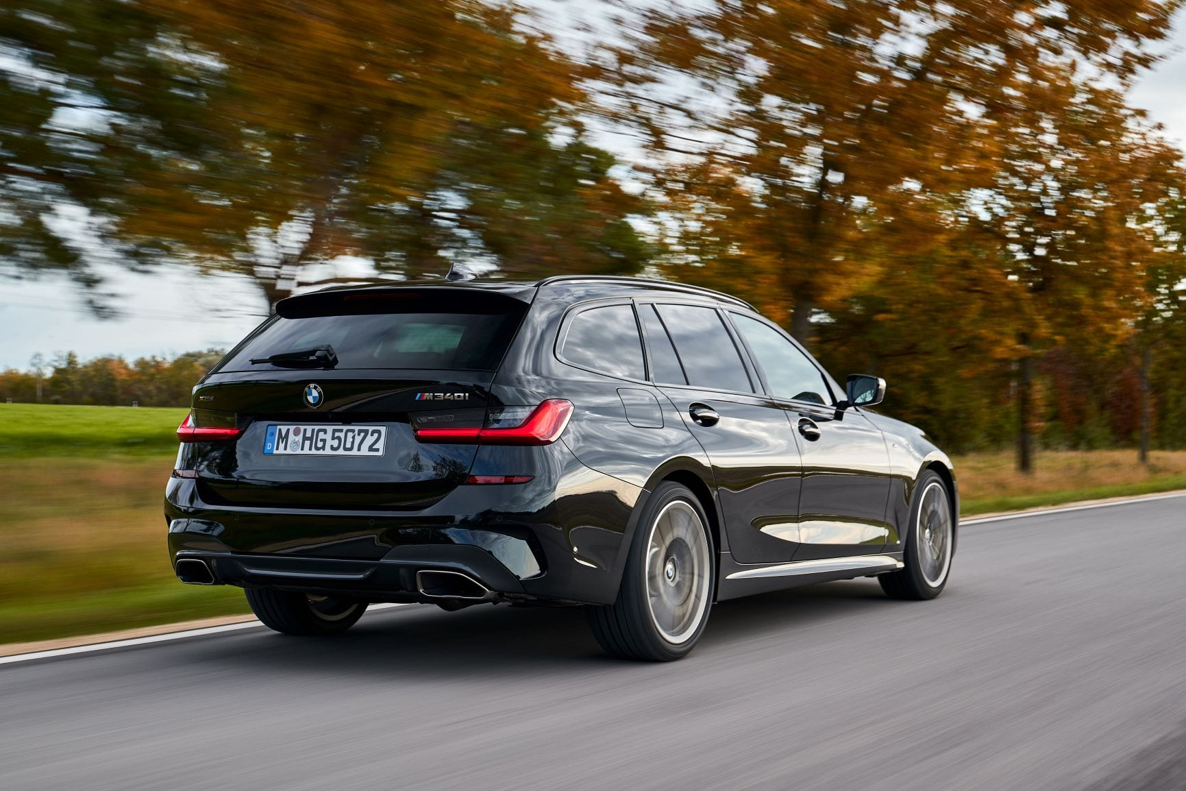 A rolling rear three quarters shot of the new BMW M340i Touring in black.
