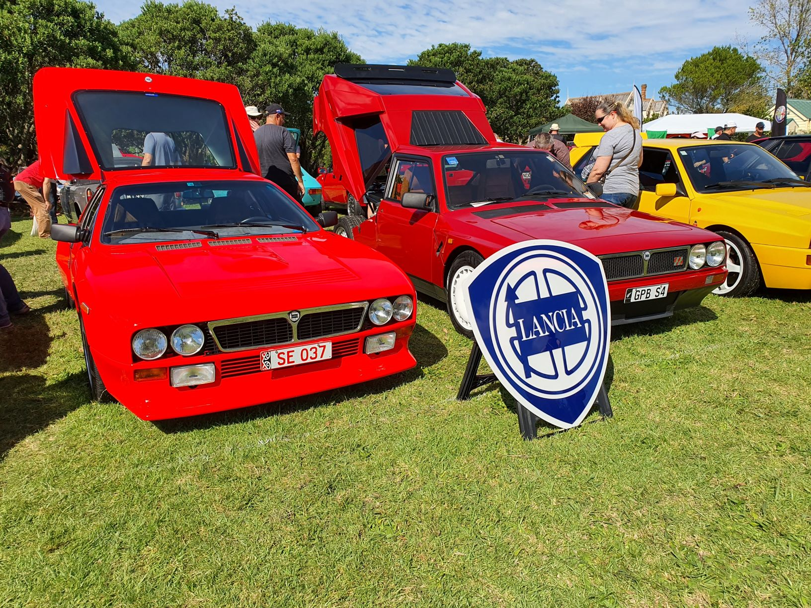 Two red Lancias, one is an 037 rally homage